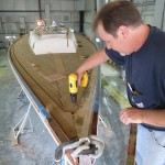 Gary from our Carpentry Shop carefully installs a custom manufactured  new teak deck for this custom built sailboat.